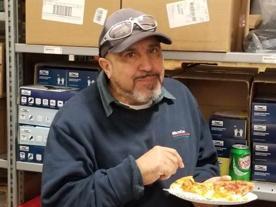 Juan enjoys a quick bite at the 35th anniversary pizza party.