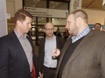 Scott Wells, MicroCare Sales Manager for Europe, speaks with two visitors from Slovakia