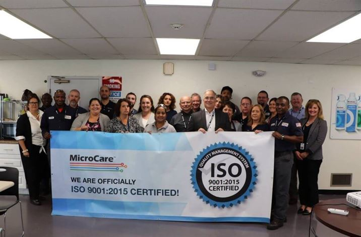 Microcare Team with the ISO Certification banner in 2018